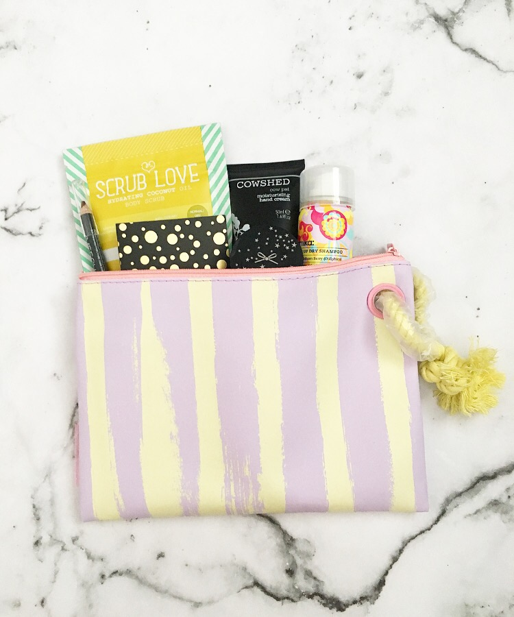 June's birchbox subscription in a pink and yellow toiletaries bag with the products poking out