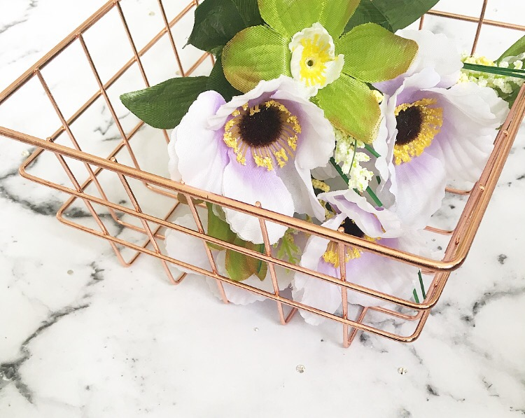 copper wire storage basket with purple flowers inside