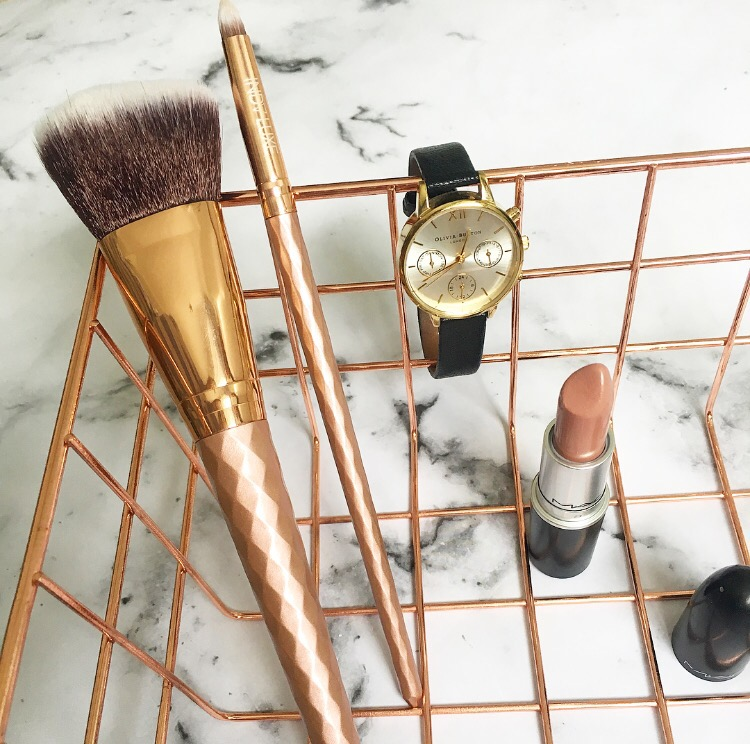 makeup brushes, a MAC lipstick and a Olivia Burton watch inside a copper wired basket